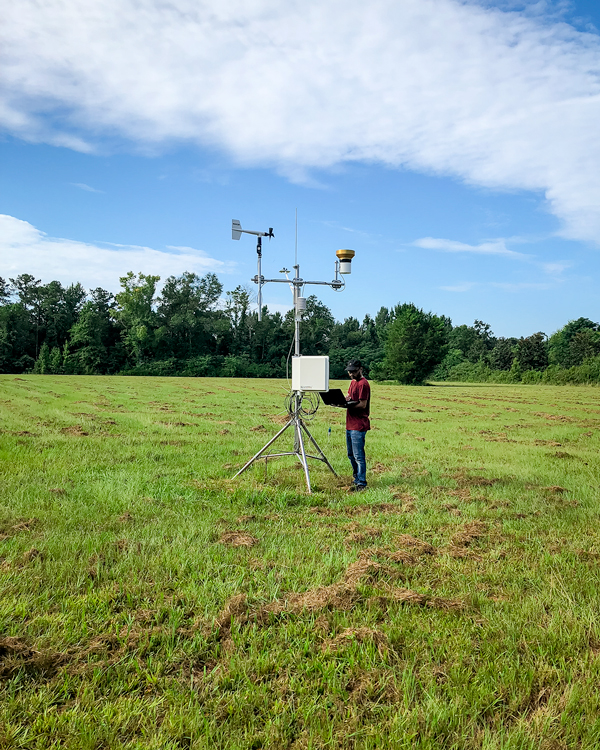 researcher collecting data from weather station
